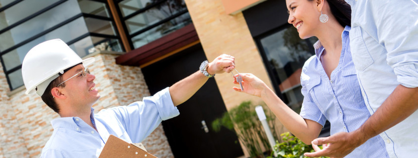 Architect handling keys of their new house to a couple